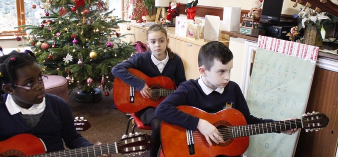 Guitarists and bell ringers perform for elderly